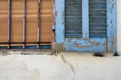 Är träslutaredörrar för gammal tappning som målas i blått, målarfärgnedgång av och trärullgardiner, brunt, det gamla fönstret på  Arkivfoto