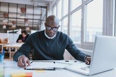 Är upptaget arbete för den afrikanska mannen på skrivbordet royaltyfri fotografi