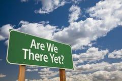 Är vi där ännu? Grönt vägmärke över himmel Arkivfoto