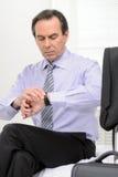 Är vilken tid det? Mogen affärsman som ser hans klocka medan s Arkivbilder
