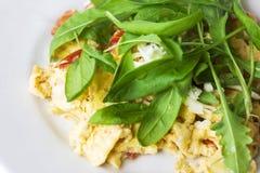 Ärgern Sie Omelett mit Tomate und frischem Arugulaspinat in der weißen Platte Stockbild
