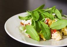 Ärgern Sie Omelett mit Tomate und frischem Arugulaspinat in der weißen Platte Stockbilder