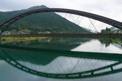 Ärke- bro över den Kiso floden med berg på bakgrunden Royaltyfria Bilder