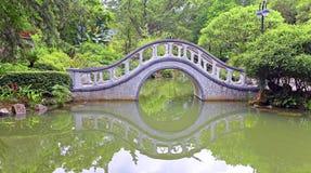 Ärke- formstenbro i trädgård Arkivfoton