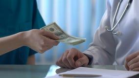 Ärlig doktor som vägrar tagandemutapengar, medicinsk affär för skugga, olagligt avtal arkivfilmer