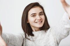 Ärliga attraktiva smilies för ung kvinna i huvudsak och sträcker händer på kameran, över vit bakgrund Flickaförsök gör Arkivfoton