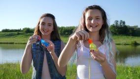 Ärliga sinnesrörelser av tonåriga flickor med såpbubblor i öppen luft stock video