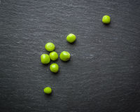 Ärtor av gröna ärtor på en svart stenbakgrund nya frukter plockning Arkivbilder