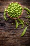 Ärtor Nya bio hemlagade ärtor och fröskidor på gammal ek stiger ombord Sund ny grön grönsak - ärtor och fröskidor Royaltyfri Fotografi