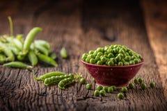 Ärtor Nya bio hemlagade ärtor och fröskidor på gammal ek stiger ombord Sund ny grön grönsak - ärtor och fröskidor Fotografering för Bildbyråer