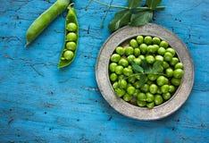 Ärtor Nya bio hemlagade ärtor och fröskidor på gammalt grönt bräde Sund ny grön grönsak - ärtor och fröskidor Arkivbilder