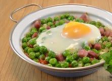 Ärtor som lagas mat med skinka och ägget Arkivbild