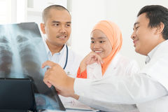 Ärzte, die auf Röntgenstrahlbild sich besprechen Lizenzfreies Stockbild