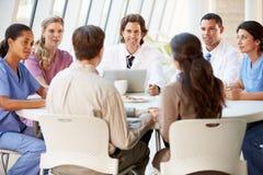 Ärzteteam, das Behandlungs-Optionen mit Patienten behandelt stockbild