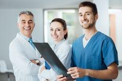 Ärzteteam, das ein Röntgenstrahlbild aufwirft und überprüft stockfotos