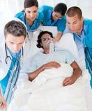 Ärzteteam, das einen Patienten trägt Stockfoto