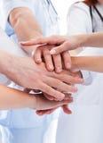 Ärzteteam, das Hände stapelt Stockbilder