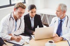Ärzteteam, das Laptop im Konferenzsaal verwendet lizenzfreie stockfotos