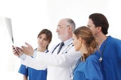 Ärzteteam, das Röntgenstrahlergebnisse überprüft stockbild