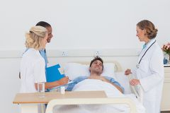 Ärzteteam, das um einem kranken Patienten sich kümmert Lizenzfreies Stockbild