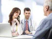 Ärzteteam mit älterem Patienten Stockfotos