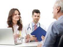 Ärzteteam mit älterem Patienten Stockbild