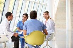 Ärzteteam-Sitzung um Tabelle im Krankenhaus Lizenzfreie Stockfotografie