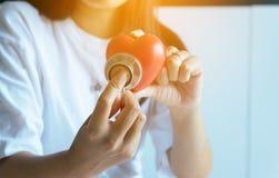 Ärztin übergibt das Halten des Stethoskops zur Prüfung des roten Herzens vom Patienten, Gesundheitswesen Konzept überprüfend Stockbild