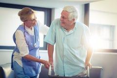 Ärztin, die älterem Mann hilft, mit Wanderer zu gehen stockbild