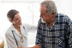 Ärztin, die älteren Mann beim Gehen am Pflegeheim unterstützt stockbilder