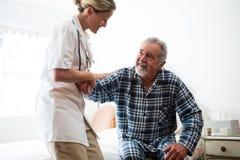 Ärztin, die älteren Mann beim Sitzen auf Bett unterstützt lizenzfreie stockfotos
