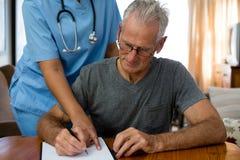 Ärztin, die älteren Mann im Schreiben am Pflegeheim unterstützt stockfotografie