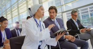 Ärztin, die über Tagebuch im Geschäftsseminar 4k sich bespricht stock video
