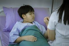 Ärztin, die auf krankem Kind-` s Bett sitzt Benutzen Sie Hand, um Hände zu halten Regen Sie geduldiges influenz an, im Krankenhau stockfoto