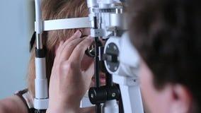 Ärztin, die Augen mit modernem medizinischem Gerät überprüft Auge, das am modernen Krankenhaus überprüft stock footage