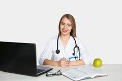 Ärztin, die bei Tisch sitzt Stockfotos