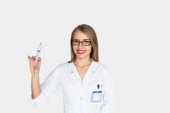 Ärztin, die das Spritzenlächeln hält Lizenzfreie Stockbilder