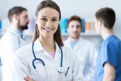 Ärztin, die an der Kamera lächelt stockbilder