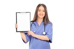 Ärztin, die ein leeres Papier auf Klemmbrett hält Lizenzfreies Stockfoto