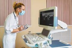 Ärztin, die ein Monitorgerät nach betrachtet Lizenzfreie Stockfotos