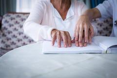 Ärztin, die einem blinden Patienten hilft, wenn das Blindenschrift-Buch gelesen wird Stockfotos