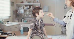Ärztin, die einen Jungen in ihrem Büro überprüft stock video