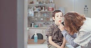 Ärztin, die einen Jungen in ihrem Büro überprüft stock video footage
