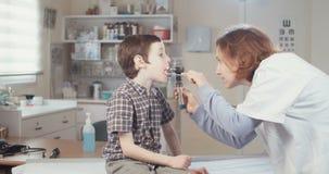 Ärztin, die einen Jungen in ihrem Büro überprüft stock footage