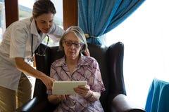 Ärztin, die Frau unterstützt, wenn Tablette am Ruhesitz verwendet wird stockfotografie