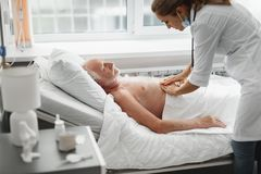 Ärztin, die geduldigen Unterleib im Krankenhauszimmer palpiert stockfotos