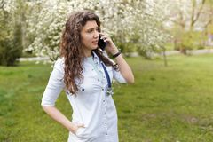 ?rztin, die am Handy spricht Kopienraum des medizinischen Hintergrundes drau?en von einem Krankenhaus im Blumengarten Nette Junge stockfotografie
