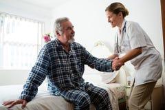Ärztin, die Mann bei der Stellung am Pflegeheim unterstützt lizenzfreie stockfotos