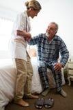 Ärztin, die Mann beim Sitzen auf Bett am Ruhesitz unterstützt lizenzfreies stockbild