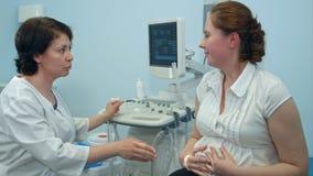 Ärztin, die medizinisches Verfahren zukünftiger Mutter erklärt Stockfoto